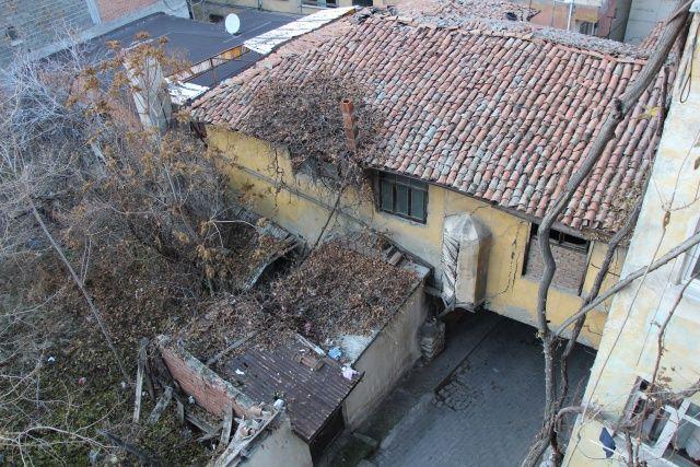 Görenler şaşıp kalıyor! Altından sokak geçen binayı ağaç direkleri ayakta tutuyor