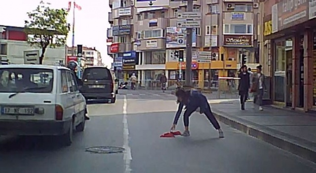 Alkışlanacak hareket! Yola düşen bayrağı, araçlar üstünden geçmesin diye aldı