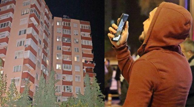 Apartmanın çatısından aşağı sarkan kadını cips yiyerek izlediler