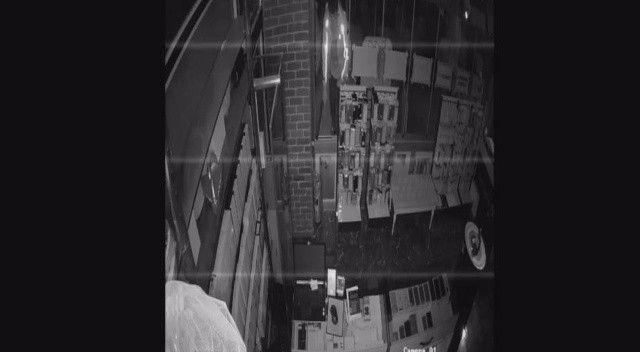 Tezgahtaki telefonları çalan şahıs içeri girdiği camı kapatarak kaçtı